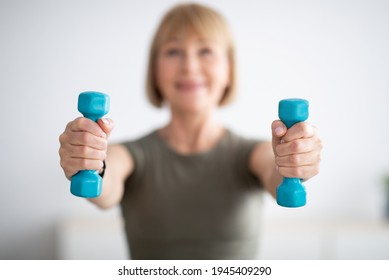Home sports during covid lockdown. Senior woman doing fitness exercises with weights indoors, focus on hands holding dumbbells. Mature lady strengthening her arm muscles, leading healthy lifestyle