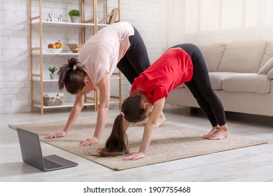 Home sports during covid. Young mother and her daughter exercising at home to online video on laptop, standing in downward facing dog pose. Parent and kid doing domestic yoga