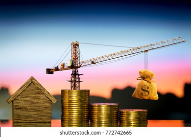 Home and stacking gold coins with increase and tower crane and hoist brake solutions with money bag to build new house in the sunset view, saving money and loan for construction real estate concept.