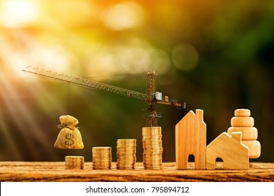 Home and stacking gold coins with increase and tower crane and hoist brake solutions with money bag to build new house in the public park, saving money and loan for construction real estate concept.