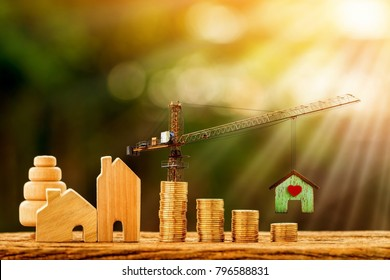 Home and stacking gold coins with increase and tower crane and hoist brake solutions with build a new house in the public park, saving money and loan for construction real estate and home concept.