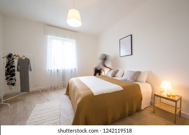 Home Staging - Home Stager woman sets up a bed in a beautiful and comfortable bedroom - Verona, Italy, June, 2018