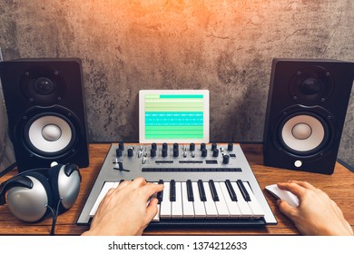home studio, music production technology concept, male musician hands playing keyboard for arranging a song on tablet computer