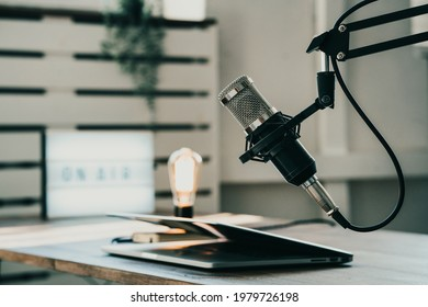 Home studio podcast interior. Microphone, laptop and on air lamp on the table