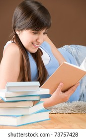 Home study - woman teenager read book lying on wooden floor