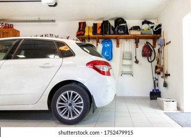 Home suburban car garage interior with wooden shelf , tools and equipment stuff storage warehouse on white wall indoors. Vehicle parked at house parking background