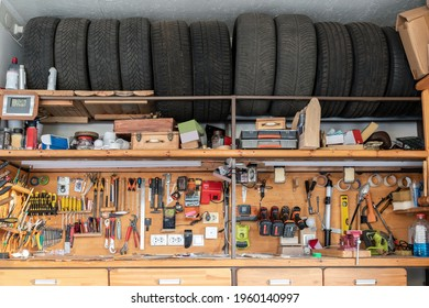 Home suburban garage interior big wooden workbench with lot of power mechanic tools at background. Spare season wheels storage shelf rack ceiling warehouse. DIY, self service and repair