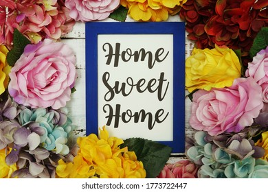 Home Sweet Home Card with colorful flowers border frame on wooden background