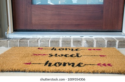 Home Sweet Home doormat. Entrance to a new Luxury House with Solid Wood Front Door with Brick front step. Welcome to Home Ownership and Suburban Living in Suburbia in Austin , Texas , USA