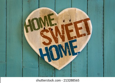 Home Sweet Home message wooden heart from recycled old palette on turquoise painted background, copy space