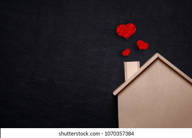Home sweet home with red heart. Wooden house and Black leather background. Happy family lifestyles and Loving people concept. Future asset between us theme. Wedding ceremony and engagement theme.