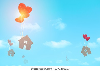 Home sweet home. home symbol with heart shape on blue sky background with copy space for text.