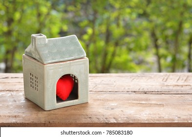 Home sweet home is where the heart is for homebuyer and real estate investment concept. Ceramic house with red heart inside on wood table over green blurred garden background.
