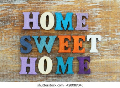 Home sweet home written with colorful letters on rustic wooden surface