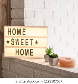 Home sweet home - it is written on a decorative frame with illumination in the interior between a white brick wall and a brown wooden one next to succulents and a pink candlestick