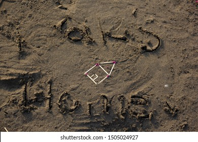 Home symbol by matchsticks on sands of a beach. Children love their home and wherever they go illustrate a home which fill safe in it.