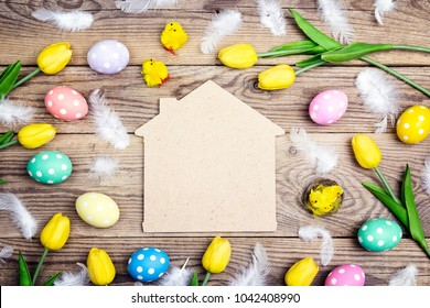 Home symbol with Easter eggs, chickens and yellow tulips on old wooden background. Space for text. Top view.