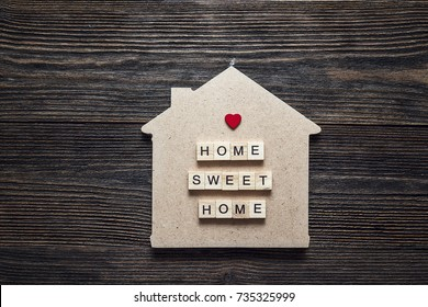 Home symbol with quote and heart shape on wooden background. Home sweet home.