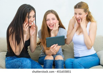 home, technology and friendship concept - three smiling girl watching something on tablet