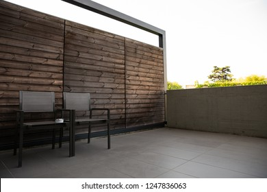 Home terrace or balcony with cozy matal chair for relaxing with wooden wall. Copy space for text or background.