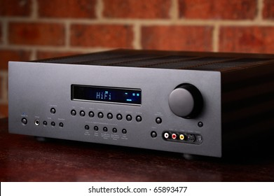 Home Theatre Amplifier A high end Hi-Fi Home Theatre Amplifier with a red brick wall backdrop. Black enclosure with blue LCD display.