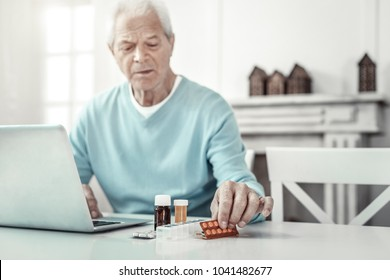 Home therapy. Sad aged serious man sitting by the table looking at the pills and using laptop.