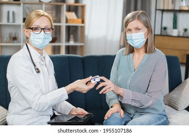 Home treatment of virus. Coronavirus pandemic. Covid-19 outbreak. Female blond doctor in face mask, examining sick patient, senior woman, measuring saturation level with pulse oximeter.