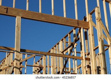 A home under construction with the focus on the window frame, against a blue sky.