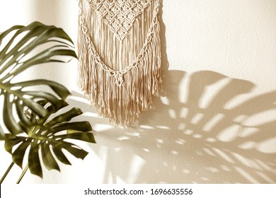Home wall decor - handmade macrame on the light wall with monstera plant. Background wallpaper.
