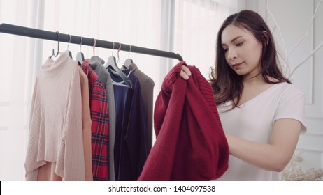 Home wardrobe or clothing shop changing room. Asian young woman choosing her fashion outfit clothes in closet at home or store. Girl think what to wear sweater.