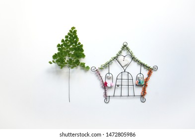 Home is where the heart is! A cute little iron house with colorful pearls beside the branch of small plant in Goiania, Goias, Brazil