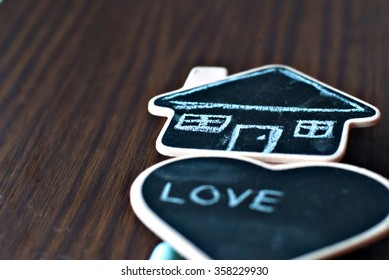 Home is where the heart is: Image of a house drawn on house shaped chalkboard with heart shaped chalkboard next to it.