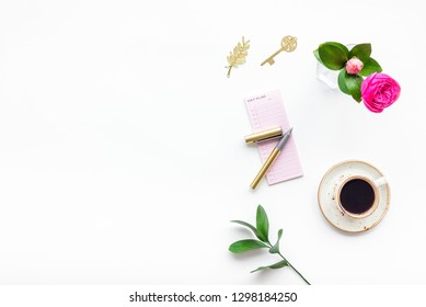 Home work desk, feminine workplace. Notebook and stationery near pink flowers and coffee on white background top view copy space