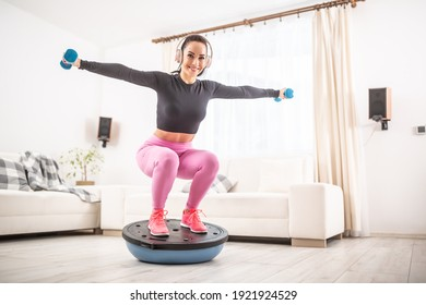 Home workout by a fit young female at home squatting on a balance ball with arms stretched to the side holding barbells..