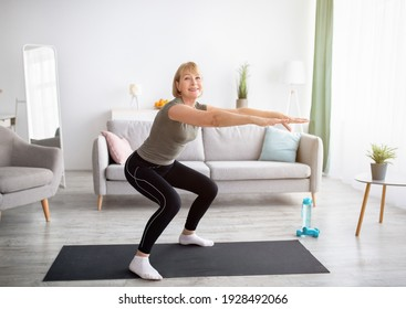 Home workout concept. Beautiful mature lady in sportswear doing squats on yoga mat indoors, free space. Positive senior woman exercising her legs on domestic training during coronavirus isolation