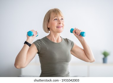 Home workout. Happy senior woman doing domestic training, exercising with dumbbells, strengthening her biceps, indoors. Fit mature lady taking care of her body, leading active lifestyle
