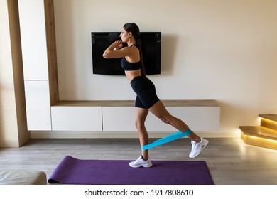 Home workout with resistance band. Girl training at home. Sports woman exercising with resistance band. Strong sporty girl in sportswear. Fitness exercise. Girl watching online tutorials on tablet.