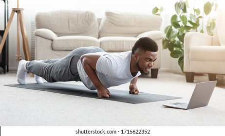Home Workout. Sporty Young Black Man Making Fist Plank Exercise In Front Of Laptop, Watching Fitness Tutorials Online, Panorama