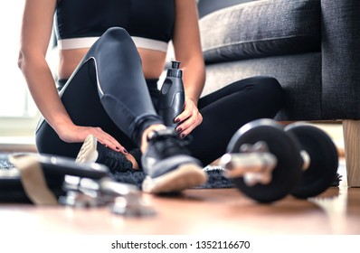 Home workout, weight training and fitness exercise concept. Woman in sportswear sitting in living room with gym equipment and dumbbell holding water bottle. Healthy sporty lifestyle. Dedicated trainer