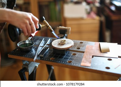 Home workshop girl master on a gas burner in a meta-liter scoop boils water with a copper plate, concept creativity and handmade, making ornaments from enamel, toning and soft focus
