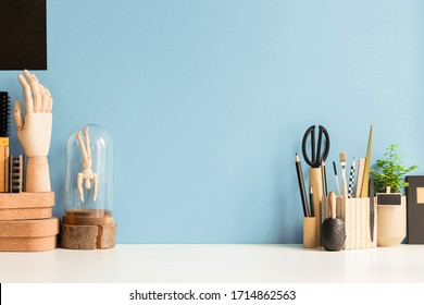 Home workspace, creative desk with wooden supplies and blue wall.