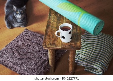 Home yoga setup with rolled up yoga mat, pillow, tea cup and cat.