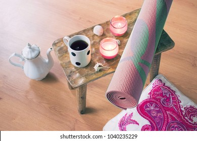Home yoga setup with tea, candles, pillow, yoga mat and natural shells. Zen accessories for meditation and relaxation at home. Top view of the floor with no people.