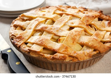 Home-baked lattice apple pie, in a brown ceramic pie plate, ready to serve.