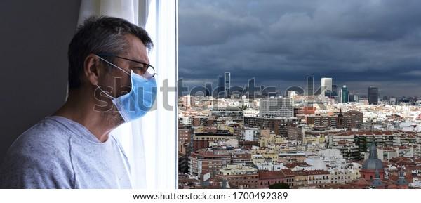 Paciente residente con mascarilla protectora mirando por la ventana al nublado horizonte de Madrid en un día tormentoso. epidemia de coronavirus.