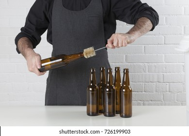Homebrewing: craft beer brewer cleaning empty beer bottles.