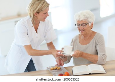 Homecarer giving tea to elderly woman