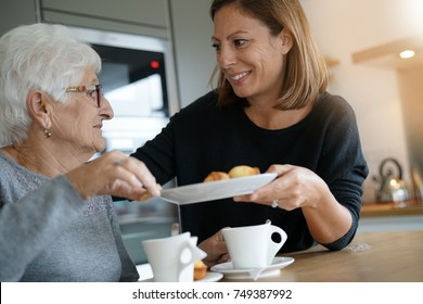 Homecarer serving tea to elderly woman