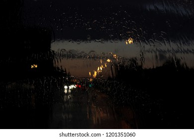 Homecoming. Bokeh lights, wet blurred view of road traffic in Gatchina on a rainy tonight through the bus front window. Raindrops and traces from the janitors on the glass window of the bus
