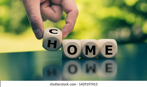 "Homecoming concept. Hand turns a cube and changes the word ""come"" to ""home""."